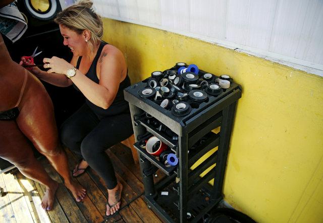Kadınlar bikini izi için koli bandıyla güneşleniyor