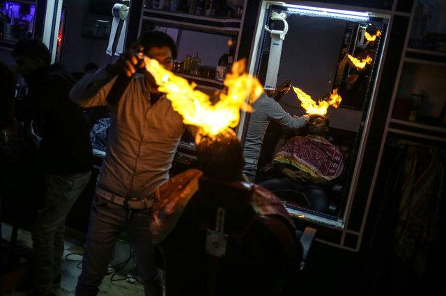 Gazzeli berber elektrikler kesilince ateşle tıraş etmeye başladı