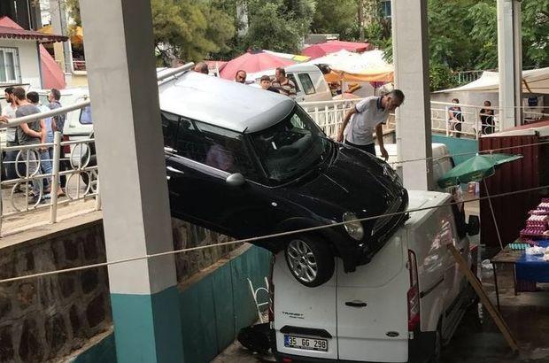 İzmir'de hakimiyetini kaybeden araç pazar yerinin üzerinde asılı kaldı