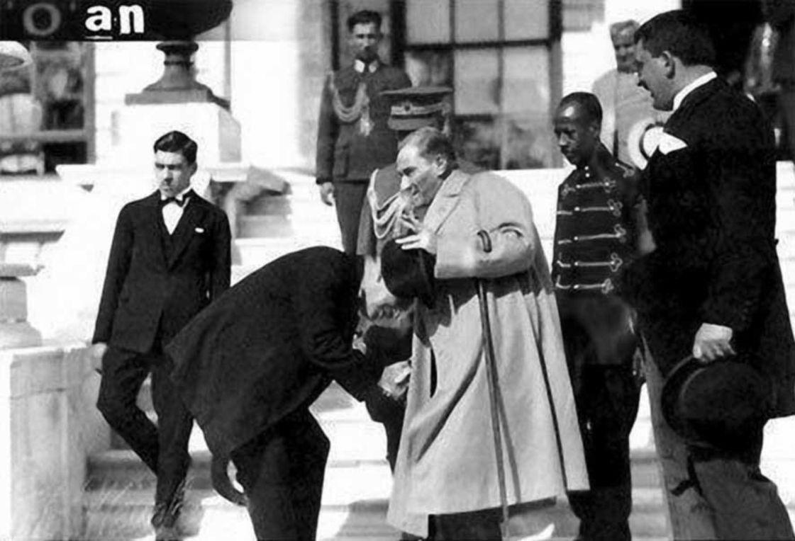 """Adamın birinin Dolmabahçe Sarayı'nın merdivenlerinin önünde Atatürk'ün elini öpmeye, Atatürk'ün de elini çekmeye çalıştığı sırada çekilen bu fotoğraf da, """"İngiliz Kralı, Atamızın elini böyle öpmüştü"""" yalanı hâline getirilmişti."""