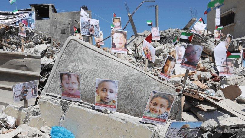 Gazze'deki bir binanın enkazı üzerinde hayatını kaybeden çocukların resimleri sergilendi