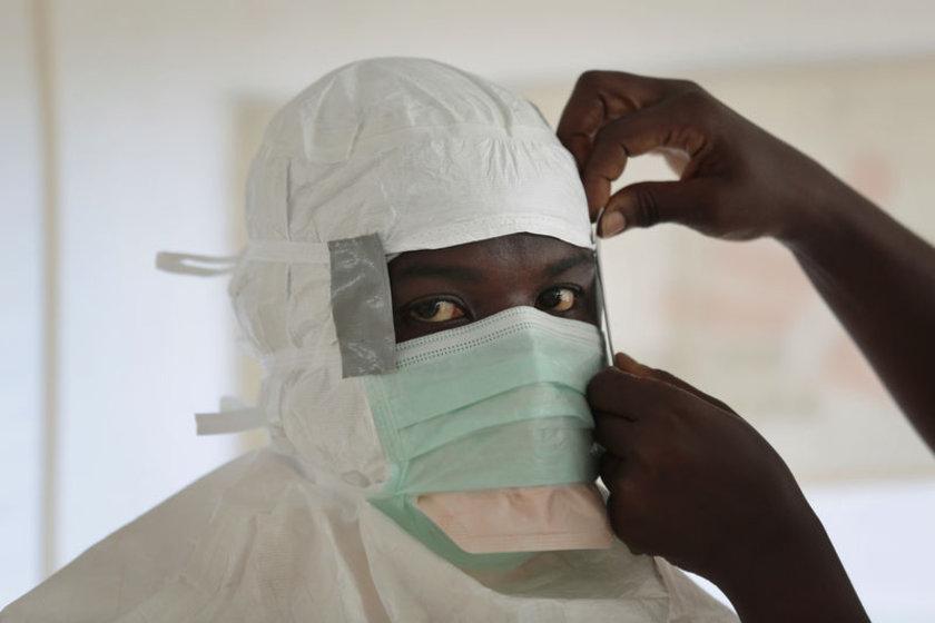 Bir sağlık görevlisi, Liberya'da yüksek risk bölgesine görmeden önce hazırlanıyor.