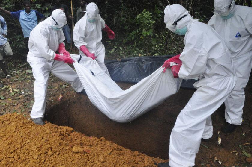 Liberya'da Ebola virüsünden hayatını kaybeden bir kadının cenazesi, yetkili sağlık ekibi tarafından defnediliyor.