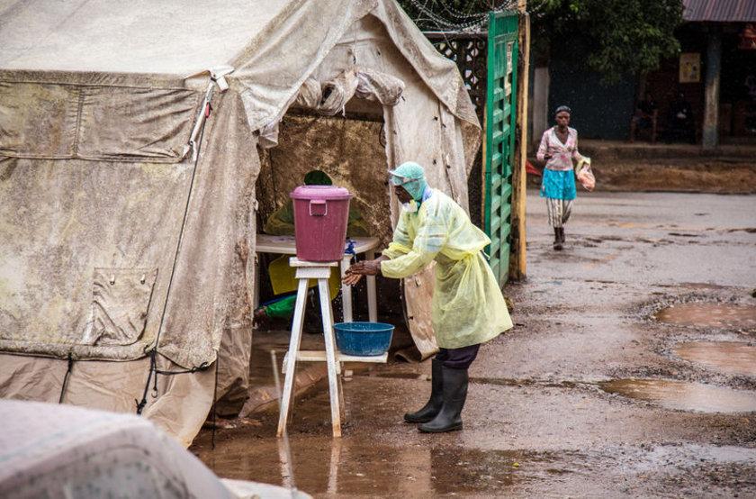 Bir sağlık çalışanı karantina bölgesine girmeden önce ellerini klorinli su ile yıkıyor.