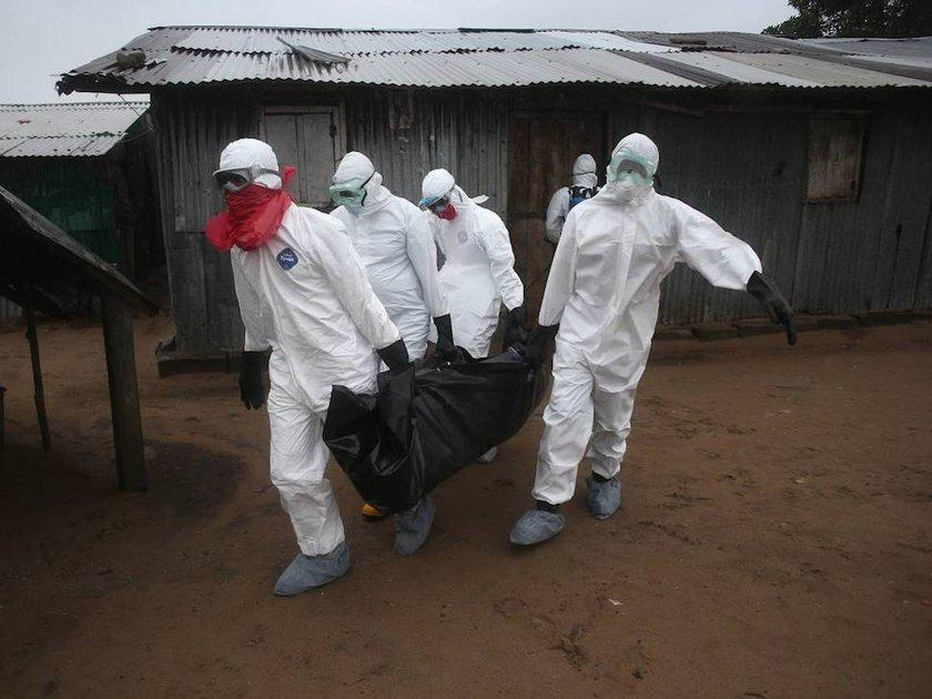 Liberya'da Ebola virüsü sebebiyle hayatını kaybeden 60 yaşındaki bir hastanın cenazesi, yetkili ekip tarafından dışarı çıkarılıyor.