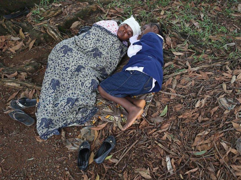 Hanah Siafa ve 10 yaşındak, kızı, Liberya'da kapasiteleri dolu olan hastaneler sebebiyle gönüllü doktorlar tarafından tedavi edilmeyi sokakta bekliyor.