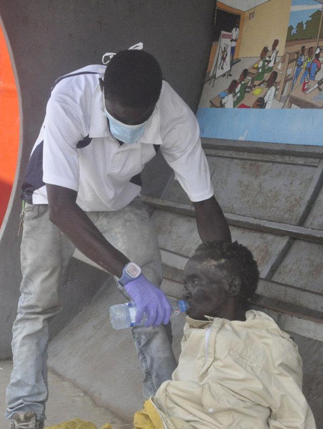 Liberya'da Ebola belirtileri gösteren bir hastaya, gönüllüler su veriyor.
