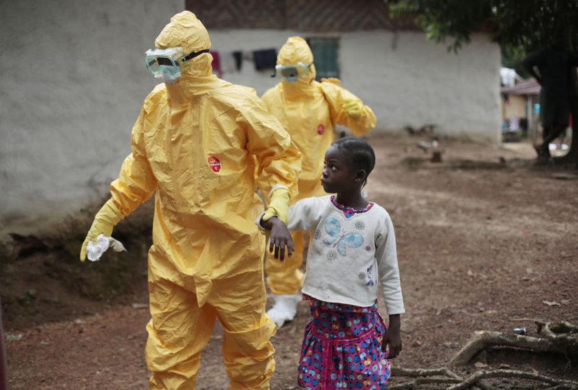 Liberya'da hastalık bvelirtileri gösteren 9 yaşındaki Nowa Paye, gönüllü doktorlar tarafından tedavi merkezine götürülüyor.