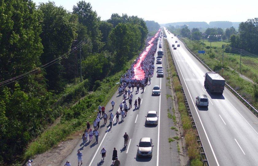 <p>Yol boyuncu uzanan bayrağı on binlerce kişi, sıcak havaya rağmen omuzlarında taşıdı.</p>