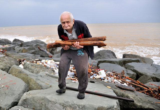 Rize'nin Çayeli ilçesinde 84 yaşındaki Cevat Ketenci, selin denize sürüklediği odunları toplayanlar arasındaydı. (DHA)