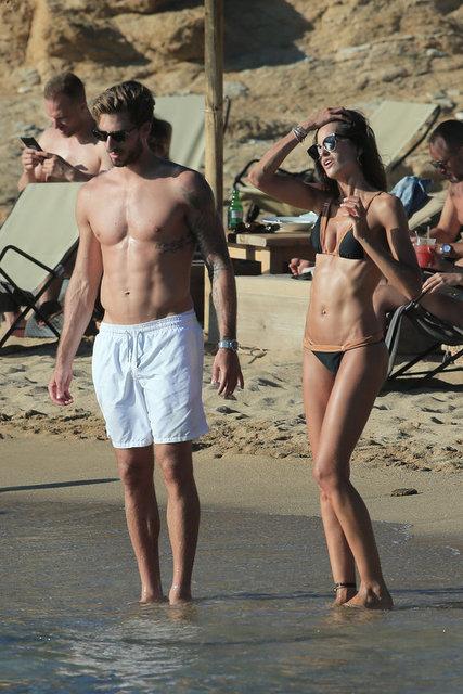 Gazete Habertürk'te yer alan habere göre, siyah parlak bir bikini giyen ve koyu renkli yuvarlak güneş gözlüğü takan model kaslı vücut hatlarıyla dikkatleri üzerine çekti.
