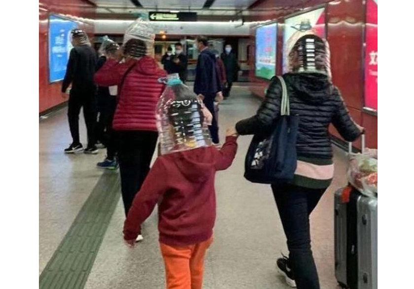 <p>Hong Kong metro istasyonunda da bir anne çocuğunun ve kendi kafasına yarısına kadar kesilmiş bir şişe geçirerek çocuğunu ve kendini virüsten korumaya çalıştı.</p>