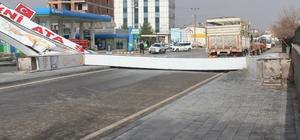 Sivas'ta kuvvetli rüzgarın etkisi ile caddeye devrilen tabela, yolu araç ulaşımına kapattı