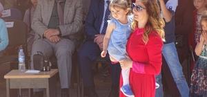 Öğretmen kucağında çocuğuyla gösteri yönetti