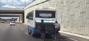 Bisikletli gençler otobüsün bagaj kapısına tutunarak yolculuk yaptı.