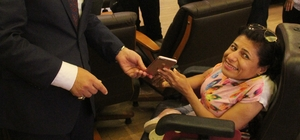 """Engelli kızın çalınan cep telefonunu emniyet müdürü teslim etti Adana'da tekerlekli sandalyesiyle evine giderken cep telefonu çalındıktan sonra zanlısı yakalanan engelli kızın telefonu da polis tarafından bulundu Engelli Ayşe Camgöz: """"Özgürlüğüm elimden alınmıştı, telefonumun geri gelmesine bayramda çok sevindim"""" Adana Emniyet Müdürü Selami Yıldız: """"En büyük mutluluk sizi tekrar sevindirmek"""""""