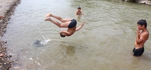 Tehlikeye aldırış etmeden nehirde yüzüyorlar Sıcak havalardan bunalan çocuklar Murat Nehri'nde serinliyor