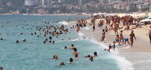 Alanya'da plajlar tıklım tıklım Kavurucu sıcaklardan bunalanlar kendilerini mavi sulara attı