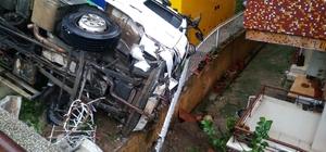 Freni arızalanan kamyon ortalığı savaş alanına çevirdi Belediye kamyonu iki arabaya çarparak bir binanın bahçesine devrildi