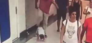 Minik çocuğa acımasız tekme kamerada Bir AVM'de çekilen görüntüde, babası olduğu iddia edilen şahıs çocuğa tekme atıyor