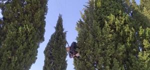 Yamaç paraşütü yaptıkları sırada ağaçta asılı kaldı Pamukkale'de yamaç paraşütüyle iniş yaparken ağaçta asılı kalan pilot ve yolcusunu itfaiye ekipleri kurtardı