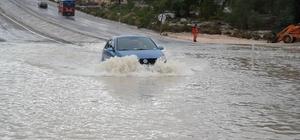 Sel suları Silifke-Mut karayolunu kapattı Bazı sürücüler çevreden buldukları tırmıkla sel suları içinde kaybolan plakalarını aradı