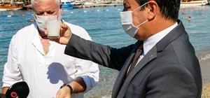 Beyaz kumun zararları gözler önüne serildi Başkan Aras masmavi denizi bembeyaz yapan beyaz kum üzerinde deney yaptı