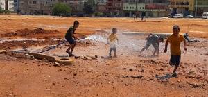 Sıcaktan bunalan çocuklar çamurda halay çekip hortumla serinledi