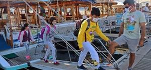 """(Özel) Mavi yolculuk gibi okul servisi Türkiye'nin tekneyle tek okul servisinde kıskandıran eğitim yolculuğu Her sabah evlerinden tekneyle alınıp turistleri bile kıskandıran yolculukla okullarına ulaşıyorlar Karayolu olmadığı için evlerinden tekne ile alınan öğrenciler, 1,6 millik tekne yolculuğunun ardından eğitime başlıyorlar Servis ücretleri devlet tarafından ödenen çocuklar, her sabah Simena Antik Kenti, tarihi kale, kaya mezarları, amfitiyatro ve eşsiz manzarayı izleyerek okula ulaşıyor Öğrencilerden Hasibe Vergili: """"Bizi biraz kıskanıyorlar gibi"""""""